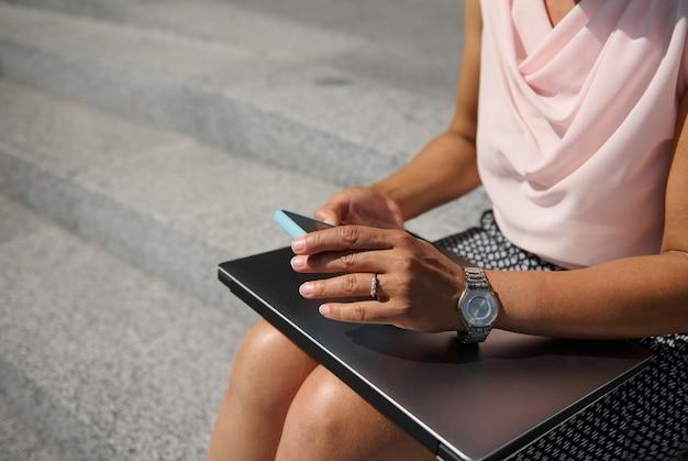 Nahaufnahme, abgeschnittene ansicht mit weichem fokus auf die hände der geschäftsfrau mit stilvoller handuhr, die ein smartphone hält und mit einem laptop auf stufen sitzt. geschäfts-, freiberufler-, online- und fernarbeitskonzept
