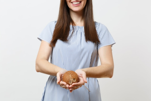 Nahaufnahme abgeschnittene fotofrau im blauen kleid halten in den händen kokosnuss oder exotische kokosnuss isoliert auf weißem hintergrund. richtige ernährung veganes vegetarisches getränk gesunder lebensstil, diätkonzept. platz kopieren
