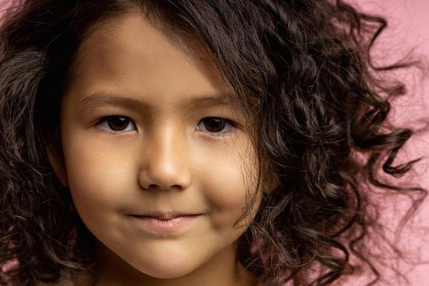 Nahaufnahme abgeschnittener kopfschuss des reizenden kindes, kleines mädchen mit dunklem lockigem haar, brauner haut, braunen augen, sanftem lächeln, direkt schauend. kinder, kinder, kindheitskonzept.