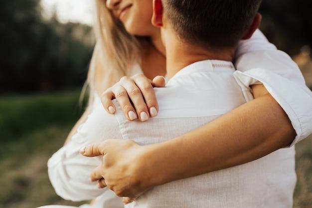 Nahaufnahme abgeschnittener schuss des jungen mannes zärtlich zärtlich eine schöne blonde frau auf den hals. weicher selektiver fokus auf der hand.