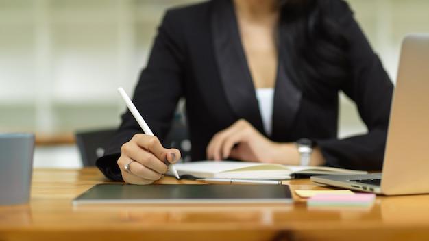 Nahaufnahme abgeschnittener schuss von geschäftsfrau mit stylus-stift mit smart-tablet auf laptop-computer