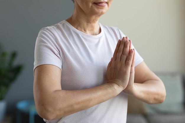 Nahaufnahme ältere frau, die meditation praktiziert