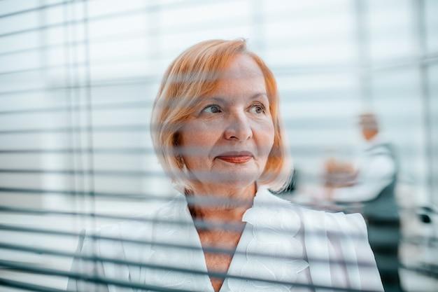 Nahaufnahme. ältere geschäftsfrau, die in einem hellen büro steht. geschäftsleute