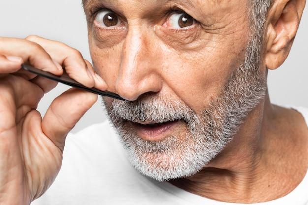 Nahaufnahme älterer mann, der haare zupft