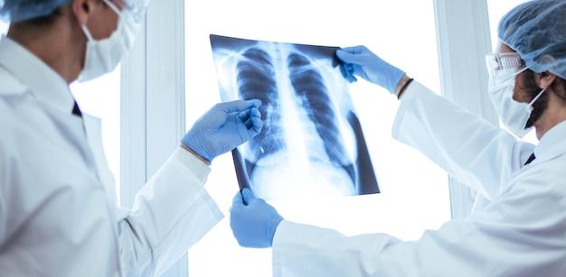 Nahaufnahme. ärzte in schutzmasken diskutieren über eine röntgenaufnahme der lunge. konzept der gesundheitsversorgung.