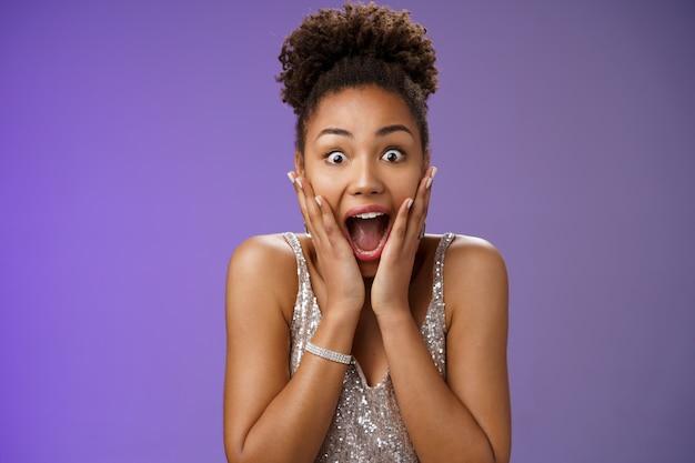 Nahaufnahme amüsiert überrascht attraktive afroamerikanische junge mädchen keuchend schreiend glücklich erhalten perfekte geschenk touch wangen begeistert lächelnd breit triumphierend feiern gute nachrichten.