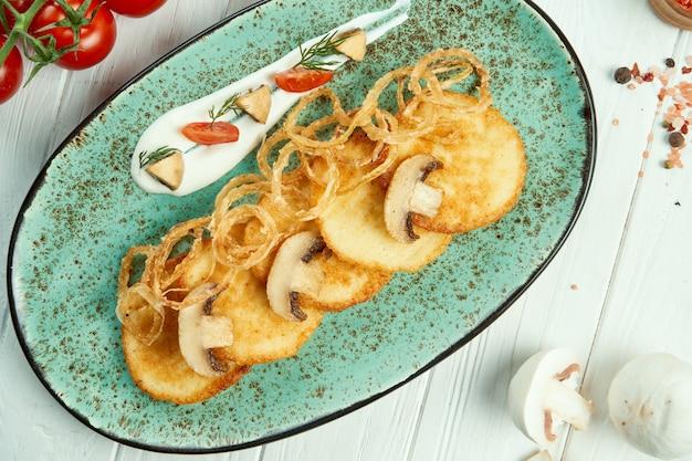 Nahaufnahme ansicht auf kartoffelpuffer mit saurer sahne und pilz auf rustikalem holztisch. draniki
