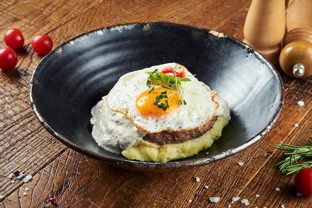 Nahaufnahme ansicht auf rindfleischsteak mit spiegeleiern, pilzcremesauce und kartoffelpüree in einer schwarzen schüssel in einer zusammensetzung mit gewürzen auf einer holzoberfläche. leckeres essen