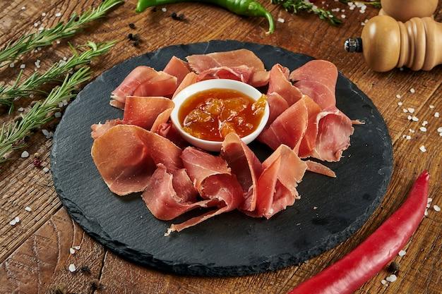 Nahaufnahme ansicht auf serrano jamon vorspeise mit süßer sauce auf einem schwarzen teller auf einer holzoberfläche. antipasti