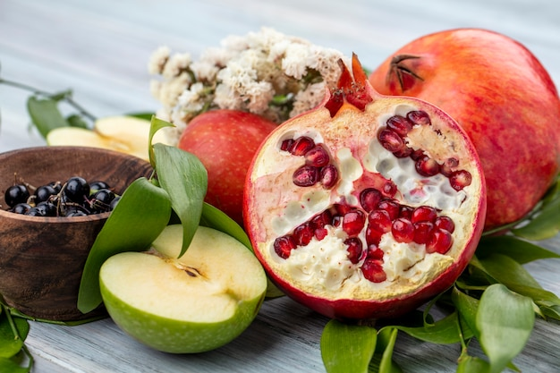 Nahaufnahme ansicht von früchten als granatapfel- und apfelhälften mit ganzen und schale der schlehe mit blumen und blättern auf schwarzer oberfläche