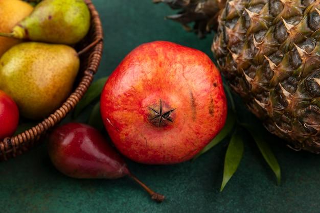 Nahaufnahme ansicht von früchten als granatapfel und pfirsich mit ananas auf grüner oberfläche
