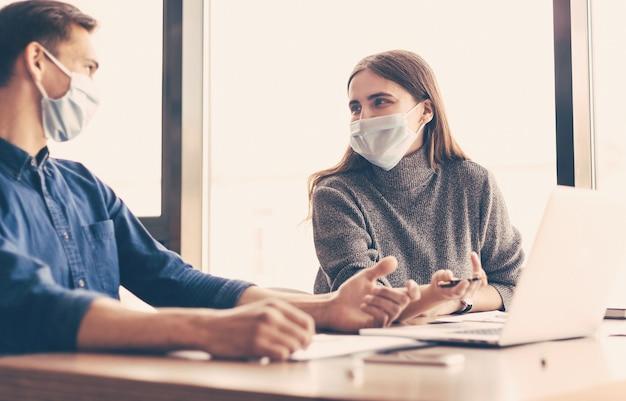 Nahaufnahme. arbeitsgruppe in schutzmasken über finanzdaten.