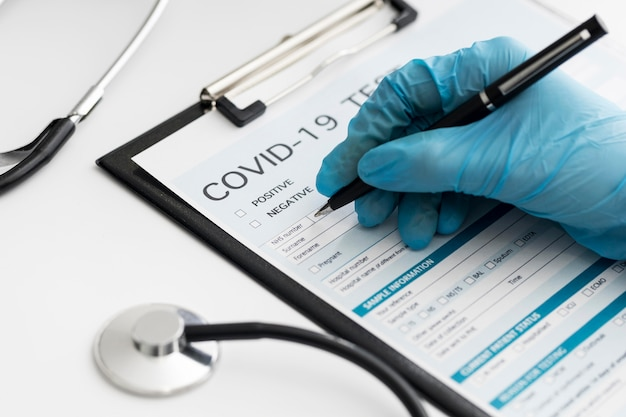 Nahaufnahme arzt, der covid medizinisches formular ausfüllt