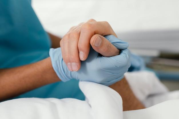 Nahaufnahme arzt und patient händchen haltend