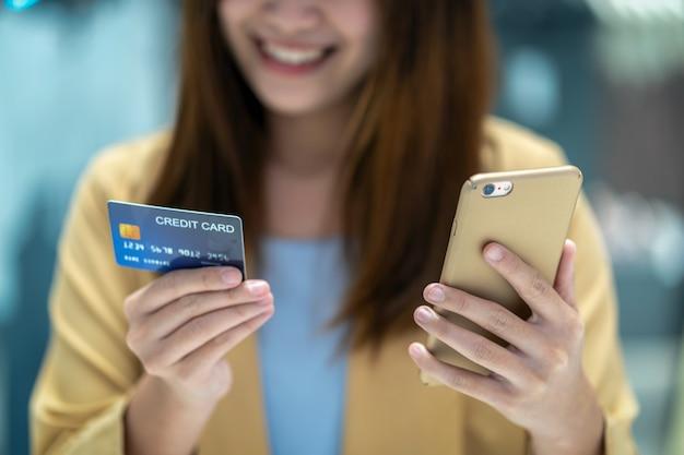 Nahaufnahme-asiatin, die kreditkarte mit mobile für das on-line-einkaufen im kaufhaus verwendet