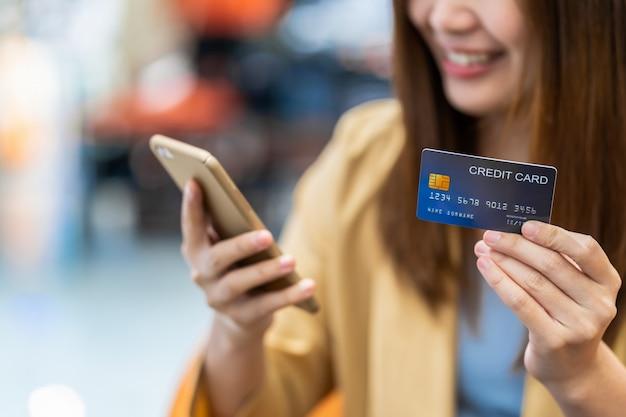 Nahaufnahme-asiatinhand, welche die kreditkarte hält und den handy für das on-line-einkaufen über der kleidungsshop-speicherwand, der technologiegeldbörse und dem online-zahlungskonzept darstellt