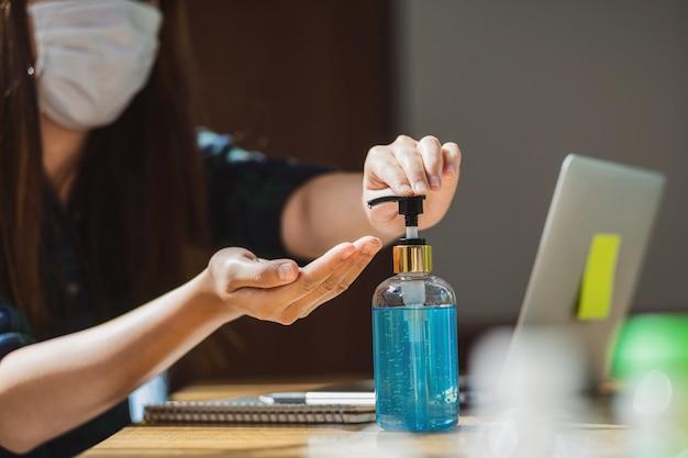 Nahaufnahme asiatische frau, die händedesinfektionsmittel durch pumpen von alkoholgel und waschen vor der arbeit verwendet