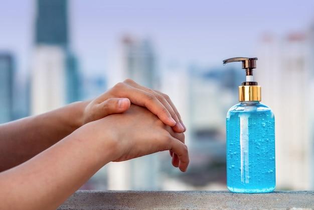 Nahaufnahme asiatische frauenhand mit waschhanddesinfektionsgel-pumpspender und medizinischer hand