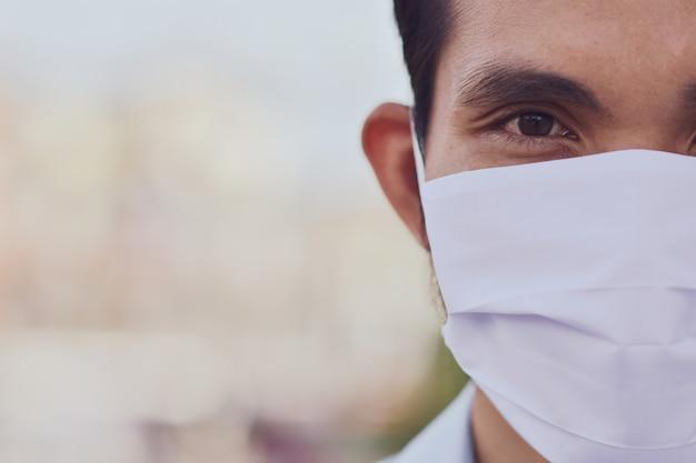 Nahaufnahme asiatische manngesichtsmaske schützen koronavirus, pm2.5 für neues normales leben soziale distanzierungskonzept