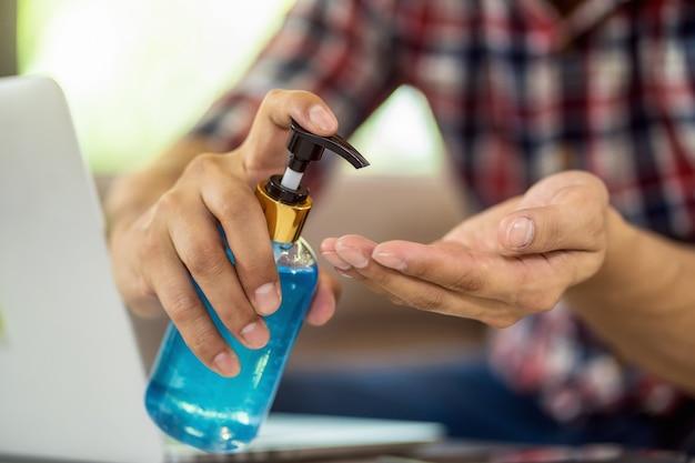 Nahaufnahme asiatischer mann mit händedesinfektionsmittel durch pumpen von alkoholgel und waschen