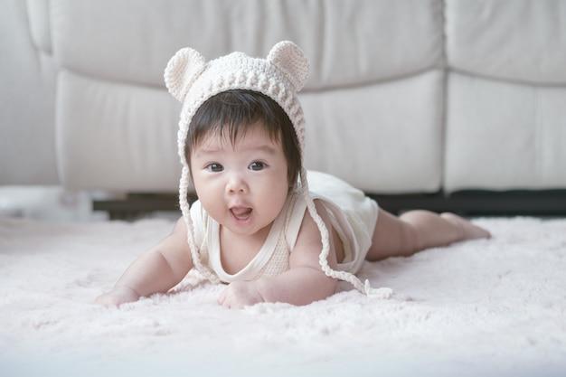 Nahaufnahme asiatisches baby liegen auf teppich in niedlicher bewegung