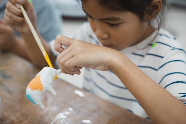 Nahaufnahme asiatisches kindermädchen konzentriert sich, um auf kleinen keramikelefanten mit ölfarbe zu malen. kreative aktivitätsklasse für kinder in der schule.