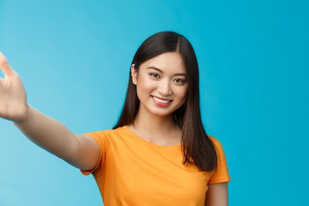 Nahaufnahme attraktives freundliches modernes vietnamesisches mädchen streckt die hand aus, nimmt selfie, lächelt freudig, macht foto-smartphone, hält den kameraarm, steht auf blauem hintergrund, fröhlicher videoanruf-freund.