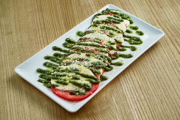 Nahaufnahme auf appetitlich italienischen caprese-salat mit frischen tomaten, weichem mozzarella, rucola und pesto-sauce auf einem weißen teller auf rustikaler oberfläche