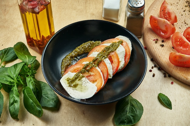 Nahaufnahme auf appetitlich machenden italienischen caprese-salat mit frischen tomaten, weichem mozzarella, rucola und pesto-sauce auf rustikalem tisch