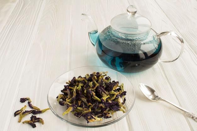 Nahaufnahme auf blauem tee in der glasuntertasse und in der teekanne
