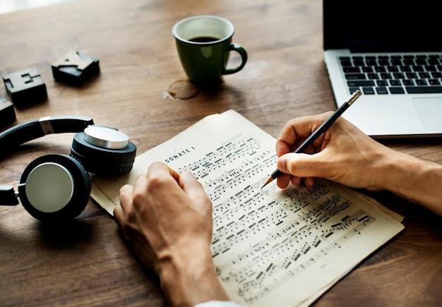 Nahaufnahme auf dem beiläufigen mann, der musik verfasst