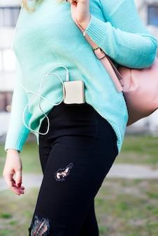 Nahaufnahme auf dem smartphone in der gesäßtasche der jeans einer frau,