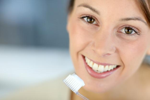 Nahaufnahme auf dem toothy lächeln der frau, das ihre zähne putzt