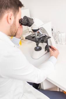 Nahaufnahme auf den arzt sieht durch das mikroskop