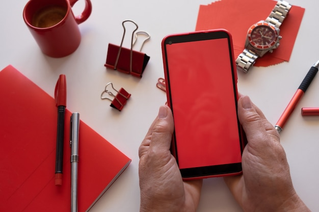 Nahaufnahme auf den händen der frau, die telefon mit rotem schirm verwendet. weißer schreibtisch und rotes zubehör