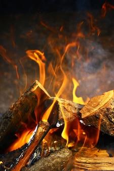 Nahaufnahme auf ein feuer über dem brennenden wald in einer feuerstelle.