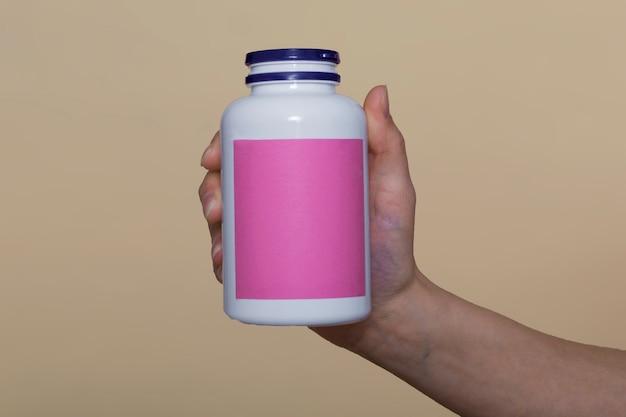 Nahaufnahme, auf einem beigen hintergrund. das mädchen hält vitamine in einer weißen flasche in der hand. vitamine für immunität, erholung. vitamine für die schönheit. platz für text
