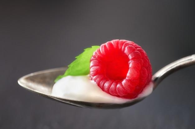 Nahaufnahme auf einem esslöffel yougurt mit juisy himbeer-nd-minzenblatt