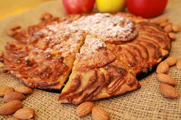 Nahaufnahme auf einem stück geschnittenem apfelkuchen mit nüssen