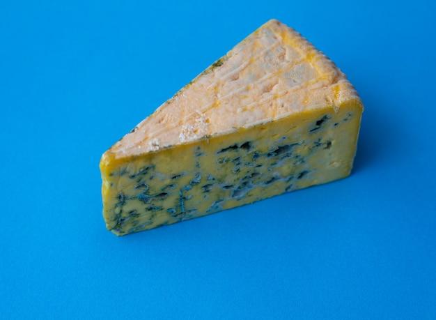 Nahaufnahme auf einem stück schimmeligen käses auf einem blauen tisch
