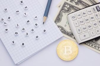 Nahaufnahme, auf einem weißen Hintergrundrechner, Geld (Bitcoin) und Notizblock mit Buchstaben