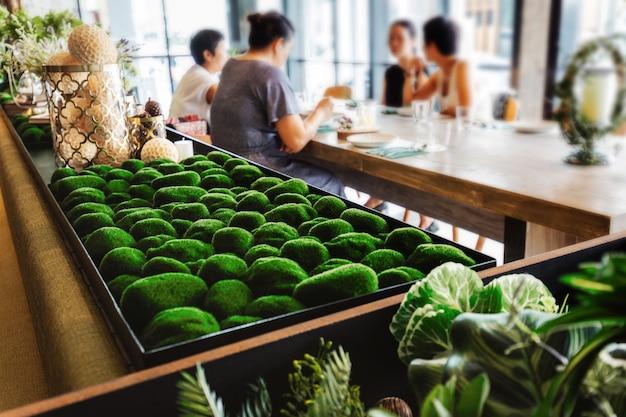 Nahaufnahme auf felsen, die mit grünem gras auf dem tisch mit verschwommener frauengruppe wickeln. moderne restaurantatmosphäre.