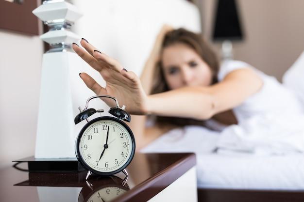 Nahaufnahme auf frauenhand, die erreicht, um wecker am morgen auszuschalten