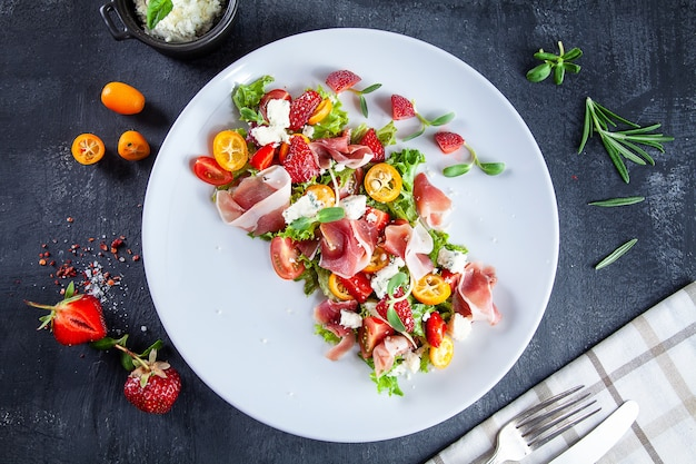 Nahaufnahme auf frischen sommersalat mit kirschtomate, erdbeere, jamon und mikrogrün. leckeres essen lag flach. essen für ein gesundes und leckeres mittagessen. speicherplatz kopieren. draufsicht