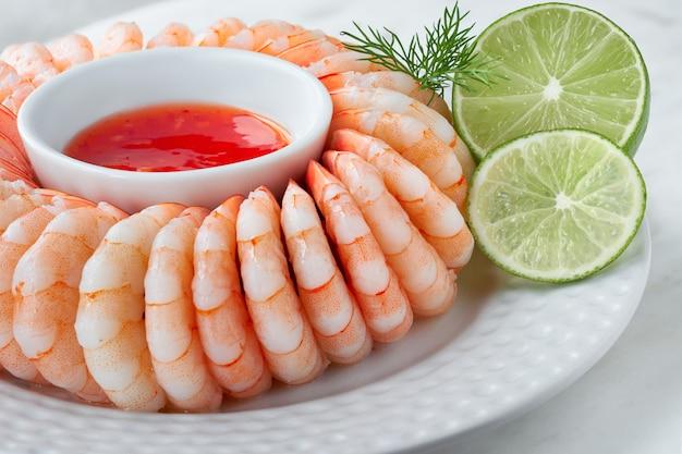 Nahaufnahme auf garnelenring mit süßem chili sause mit dill und kalk