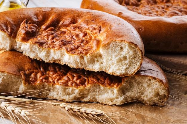 Nahaufnahme auf gebrochenem frisch gebackenem zwiebelfladenbrot