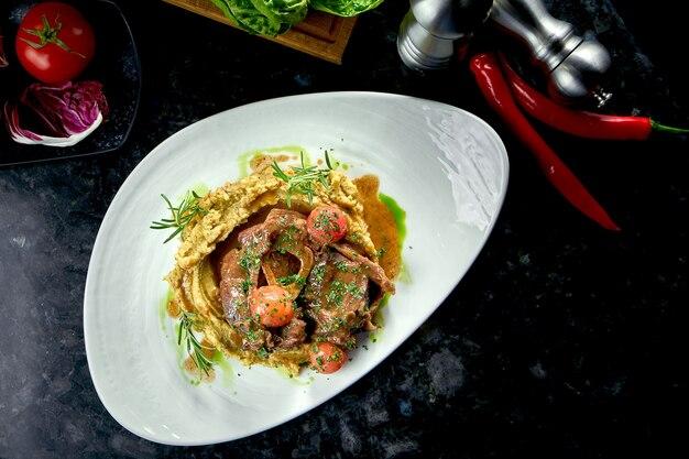 Nahaufnahme auf gedünstetem osso buco-steak mit tomaten, kartoffelpüree, serviert in einem weißen teller auf einem dunklen marmortisch. italienisches steak. restaurant essen