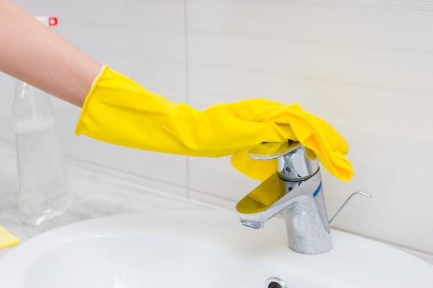Nahaufnahme auf gelben gummihandschuh, der den chrom-waschbeckenstutzen mit einem weichen tuch neben der klaren sprühflasche im badezimmer reinigt