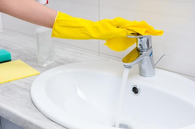 Nahaufnahme auf gelber hand mit gummihandschuhen, die den wasserfluss vom chromhahn in das elfenbeinfarbene waschbecken mit sprühflasche und schwämmen daneben überprüft