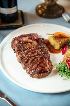Nahaufnahme auf geschnittenem gegrilltem rindfleisch-ribeye-steak mit kartoffeln auf weißem teller